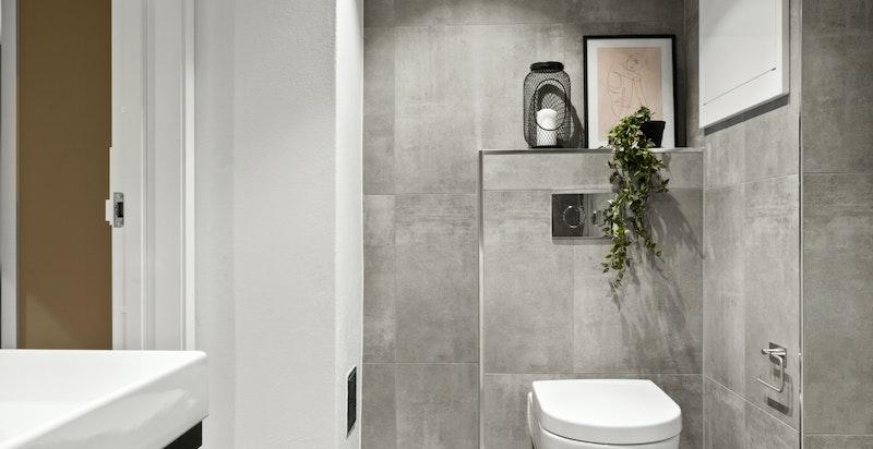 Badet er videre utstyrt med veggehengt wc, servant med skuffer under og dusj i hjørne med innadslående dører.