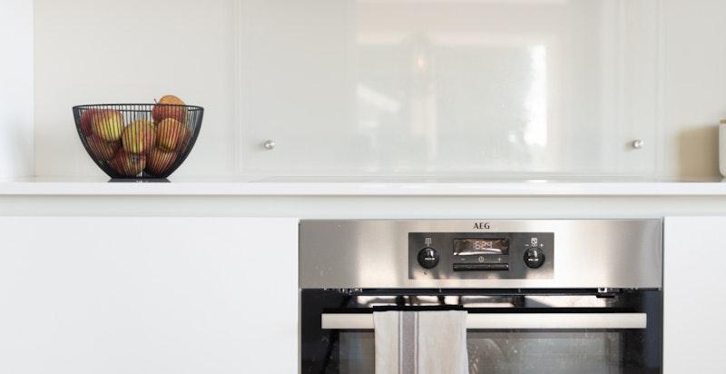 Innredningen består av kompositt benkeplate og noe glass over benk. Det er integrert komfur, induksjon platetopp, oppvaskmaskin og kjøl/frys.