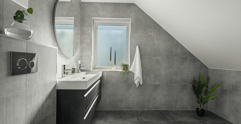 Badet er utstyrt med vegghengt wc, dobbel servant med skuffer og frittstående badekar.