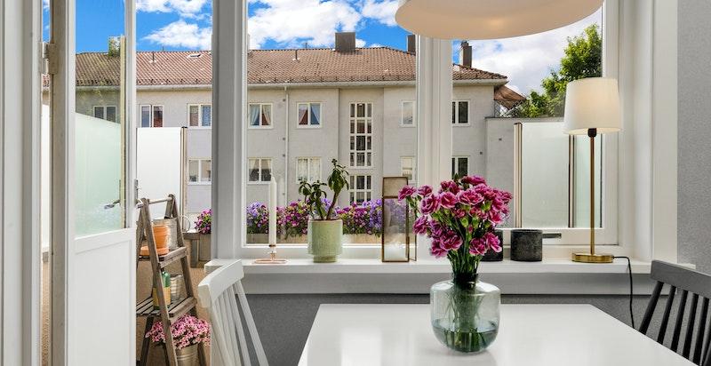Hyggelig plassert spisebord ved vinduet med flott utsyn over borettslagets grønne fellesareal.