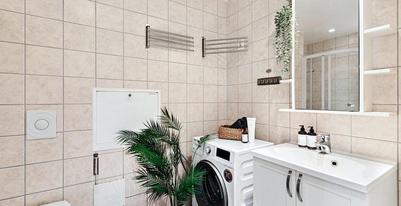 Flislagt baderom med varmekabler i gulv - Vegghengt toalett, dusjnisje og servantinnredning for oppbevaring