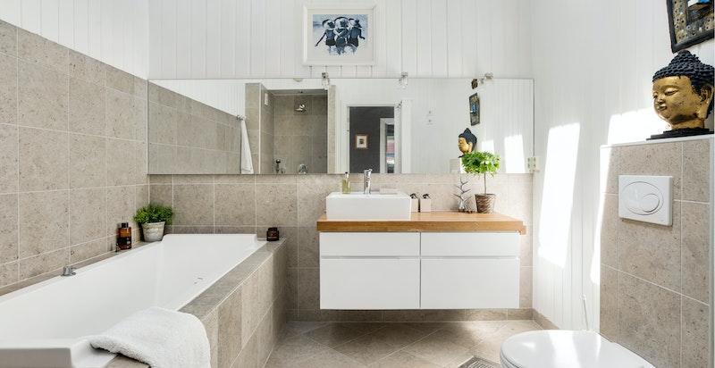 Badet er romslig med god takhøyde og er utstyrt med både badekar og dusjhjørnet