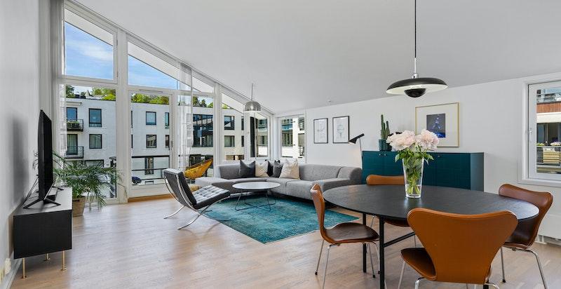 Romslig stue i hovedetasje (5. etg.) med spektakulær takhøyde og store vindusflater. Utgang egen vestvendt kveldssolbalkong