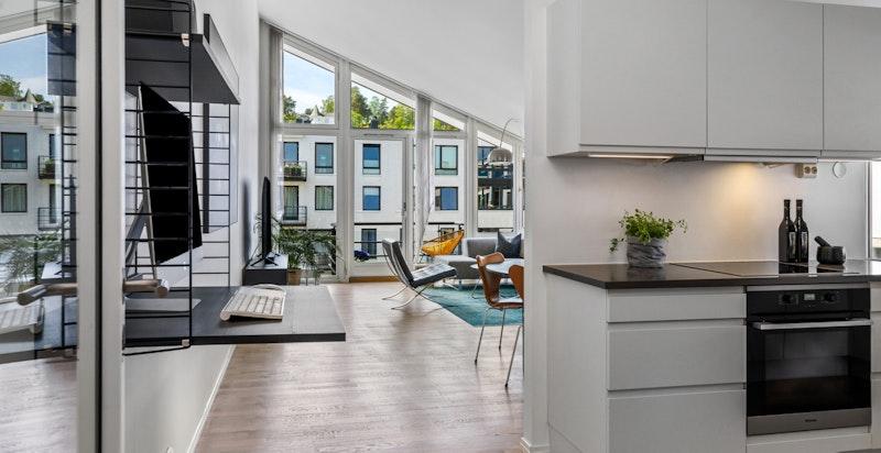 Hovedetasjen tilbyr romslig stue med utgang kveldssol-balkong og et tiltalende delvis åpent kjøkken
