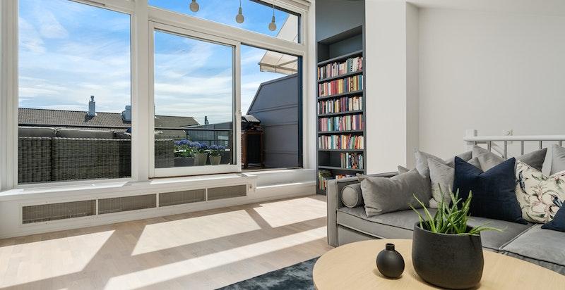 Loftsstue med store vindusflater. Her ser man mye himmel og det er rikelig med naturlig lysinnslipp. Tilpasset solskjerming