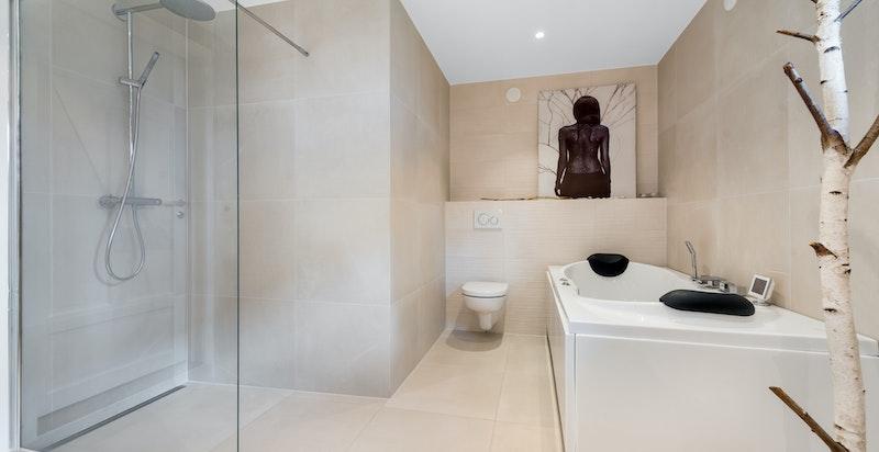 Flislagt baderom i underetasjen med gulvvarme, massasjebad med blåtann og dusjnisje
