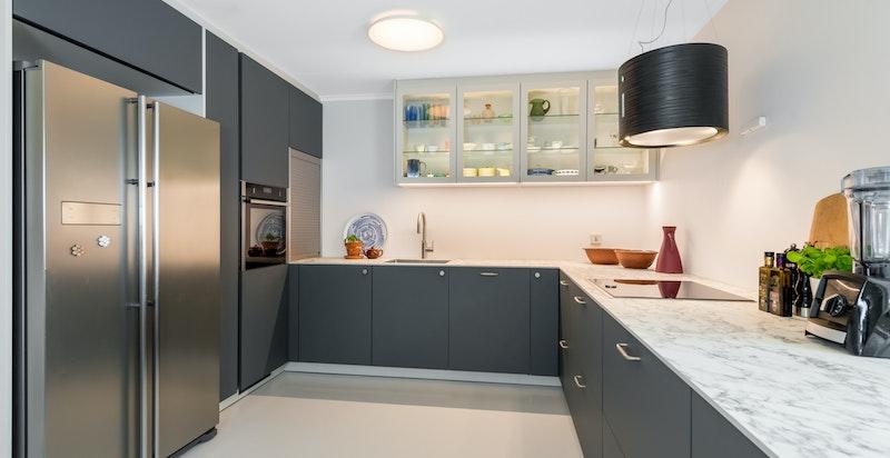 Moderne kjøkken med hvitevarer og godt med benk- og skapplass