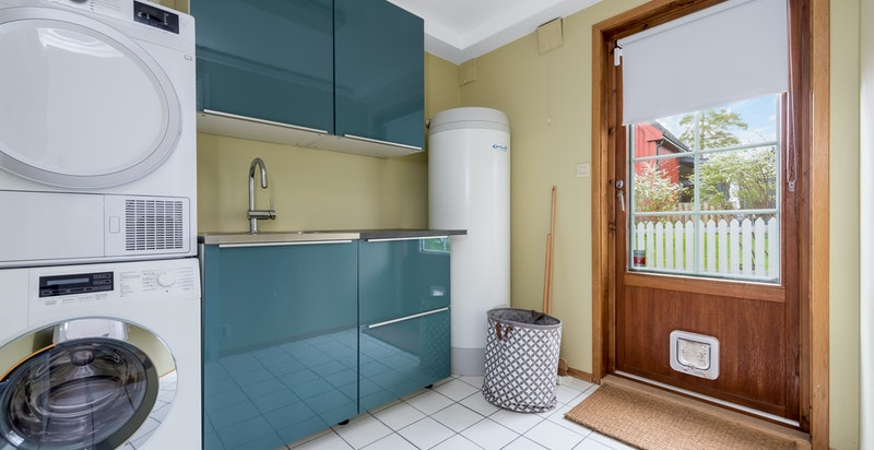 Vaskerom med vaskemaskin og tørketrommel samt utgang til hage