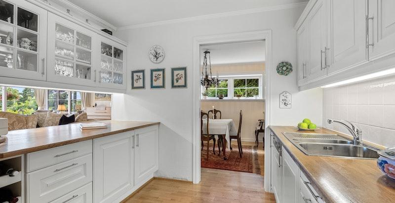 Kjøkken med hvite profilerte fronter på skuffer og over-/underskap. Gjennomgående vitrineskap mellom stue og kjøkken.