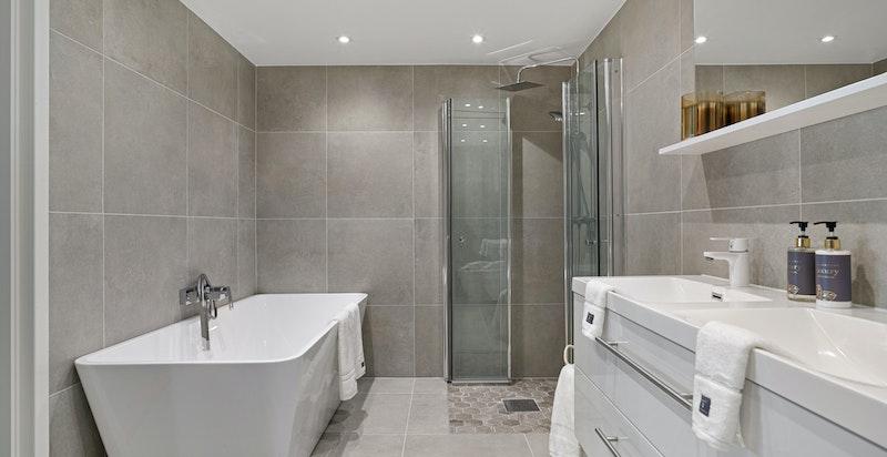 Delikat og innbydende hovedbad fra 2021 med både dusj og design badekar. Elektriske varmekabler i gulv. Downlights i himling