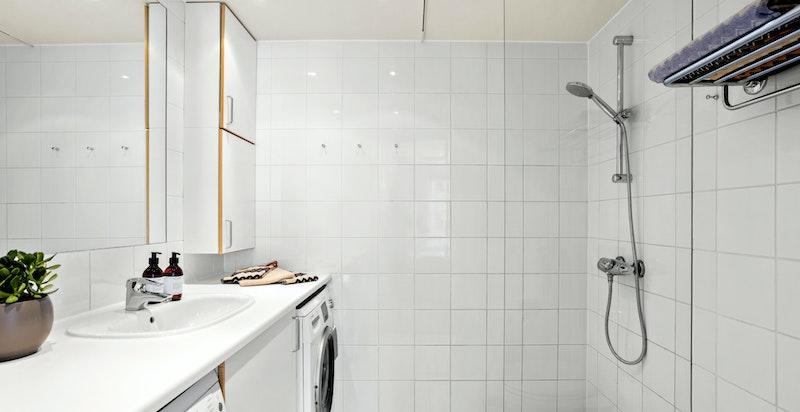 Badet ligger med direkte adkomst fra soverommet med en lys og tidløs innredning.