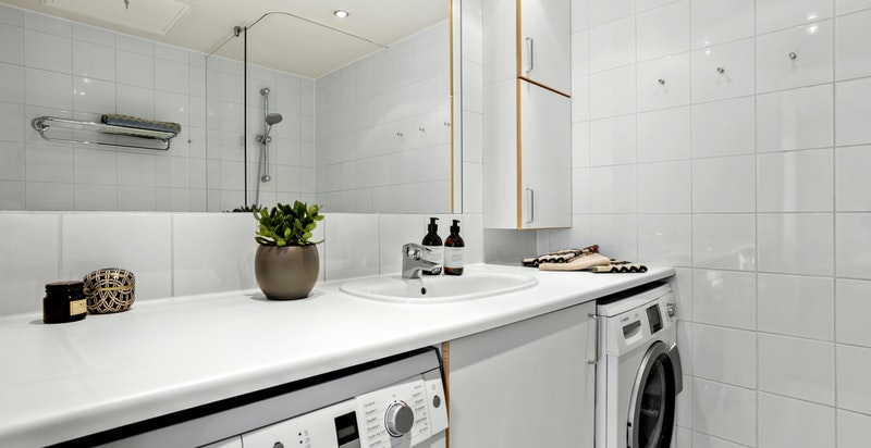 Det er opplegg for både vaskemaskin og tørketrommel i praktisk løsning under servantinnredningen.