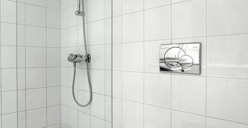 Videre er badet utstyrt med vegghengt wc og dusj i hjørne med glassvegg. Det er behagelige varmekabler i gulvet.