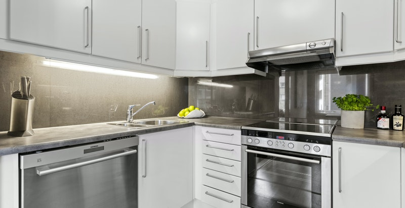 Det er laminat kjøkkeninnredning og benkeplate, fliser over benk, ventilator vifte og nedfelt kum.