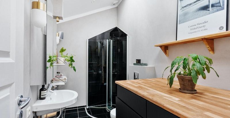 Pent baderom med fliser på gulv - Dusjnisje og vegghengt toalett - Opplegg og plass til både vaskemaskin og tørketrommel i snekkerbygd møbel