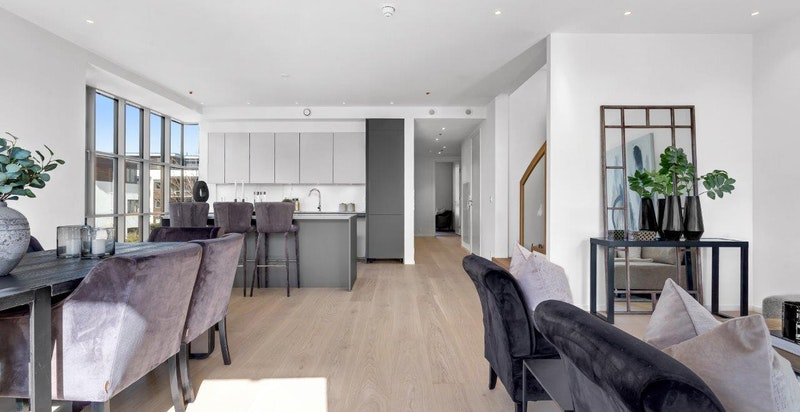 Innholdsrik og romslig stue/kjøkken med god plass til både spisebord og sittegruppe.