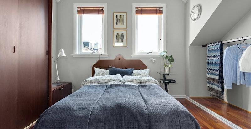 Romslig soverom med god plass til dobbeltseng, skap og klesoppheng.