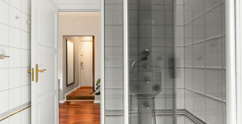Badet er utstyrt med wc, søyleservant, dusj i hjørne med innadslående dører og innmurt badekar.