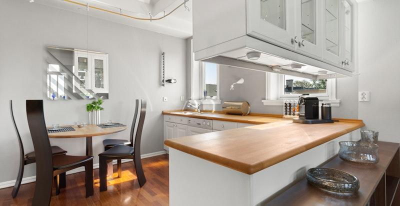 Kjøkkenet er lyst og hyggelig med profilert høyglans Siemattic kjøkkeninnredning i hvit.