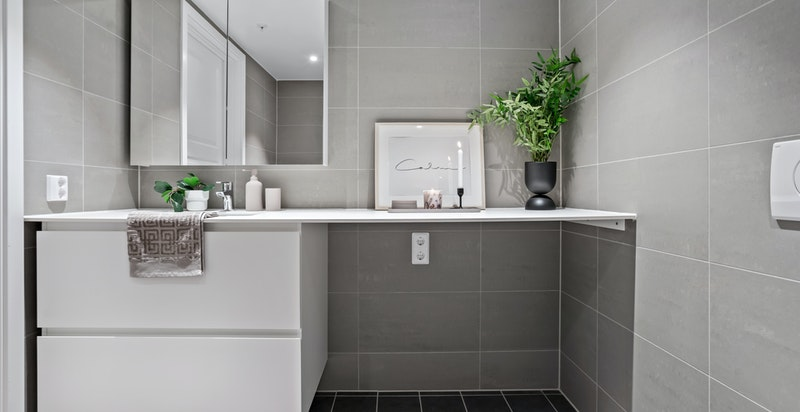 Badet har vegghengt toalett, dusjhjørne og opplegg til vaskemaskin og tørketrommel.