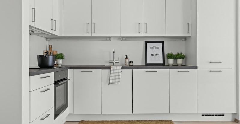 Kjøkkeninnredningen har hvite glatte fronter kombinert med laminat benkeplate.