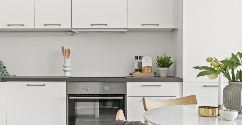 Kjøkkenet har hvite glatte fronter og laminat benkeplate.