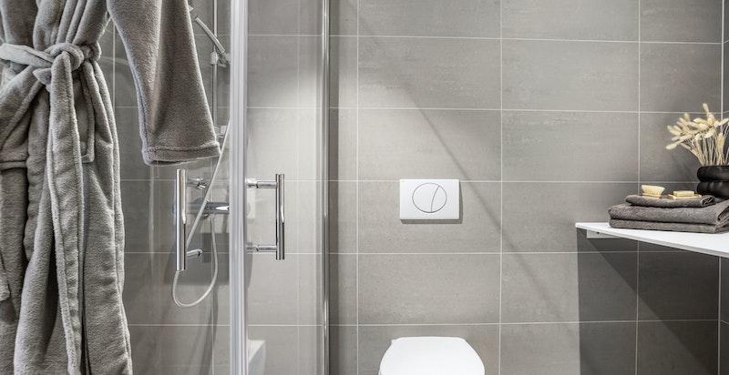 Badet har moderne innredning og opplegg til vaskemaskin.