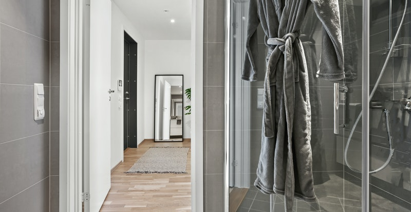 Det er vegghengt toalett og dusjhjørne med innfellbare glassvegger.