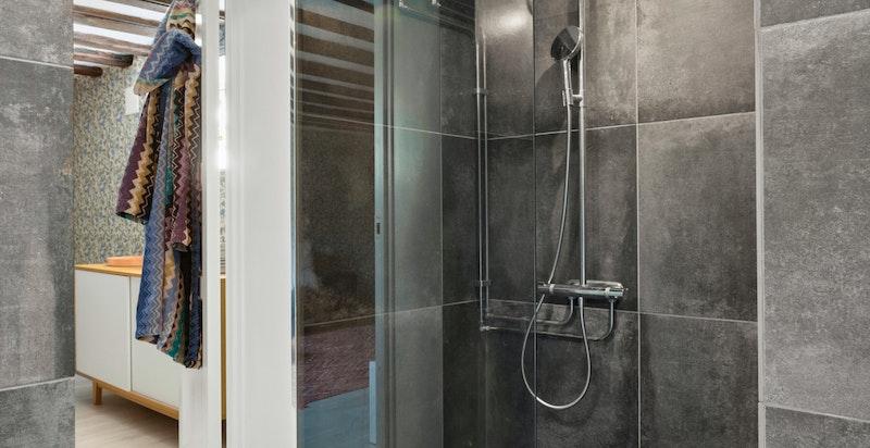 Badet er videre utstyrt med vegghengt wc, servant på benkeplate med underskap og dusj i hjørne med glassvegg.
