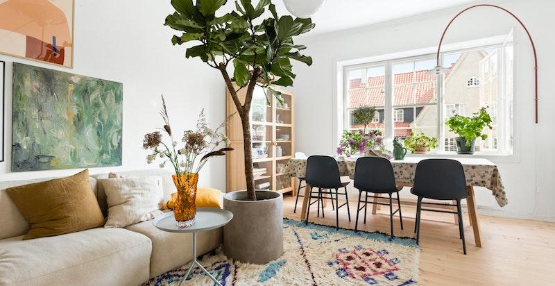 Fra entréen blir du møtt av en lys og innbydende stue. Etasjen har en åpen romløsning, men sørger likevel for naturlige soner for både sofaseksjon og romslig spisebord med plass til flere gjester.