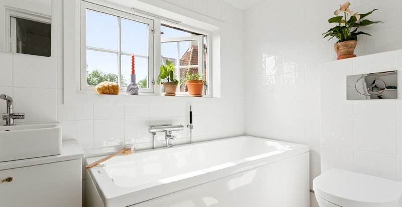 Badet i 2.etasje er lyst og tidløst med vegghengt wc, servant med skuffer og badekar.