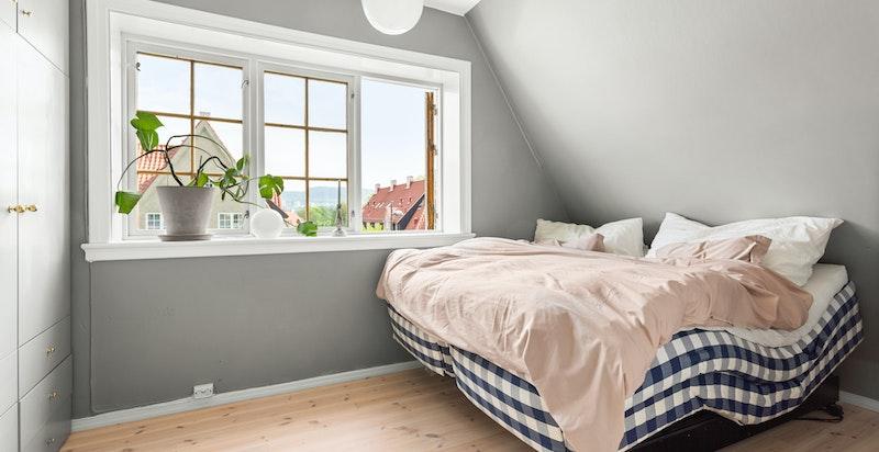 Hovedsoverommet er malt i fargen Manor House fra Farrow & Ball, en trendy og fin gråtone som står i fin kontrast til de hvite vinduskarmene.