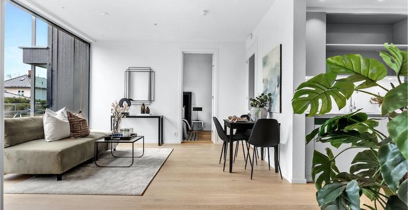 Stue med delvis åpen kjøkkenløsning. Store vindusflater slipper inn rikelig med lys.