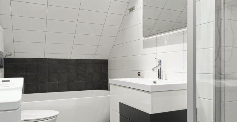 Badet i loftetasjen er innredet med taoeltt, servantinnredning, Tylö steamdusj, frittstående badekar og opplegg for vaskemaskin.