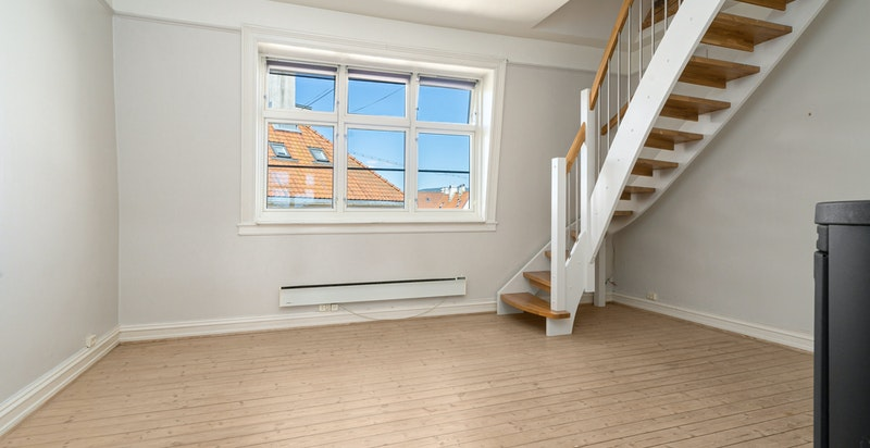 Romslig stue med god plass til sofagruppe og tilhørende møblement.