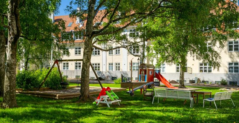 Utenfor leiligheten er det hyggelige bakgård med lekeplass og sittegrupper.