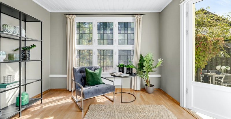I tillegg til vanlige vinduer har stuen også terrassedør og et flott originalt blyglassvindu
