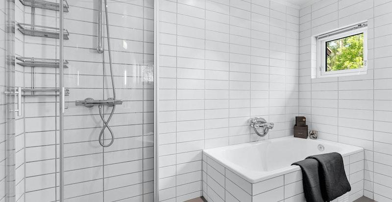 Badet er innredet med dusjhjørne med innfellbare dusjdører, badekar, søyleservant, downlights og elektrisk avtrekksvifte i taket