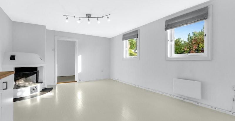 Hyggelig kjellerstue med peis og to store vinduer i kjellerstuen som gir godt med lysinnslipp