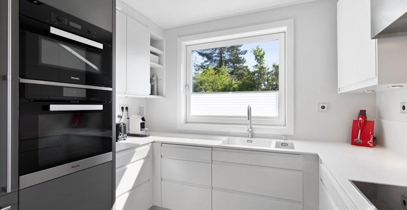 Innholdsrikt kjøkken med integrerte hvitevarer som komfyr, mikrobølgeovn, stort vinskap, oppvaskmaskin, steketopp og ekstra bredt kombi kjøl/frys.