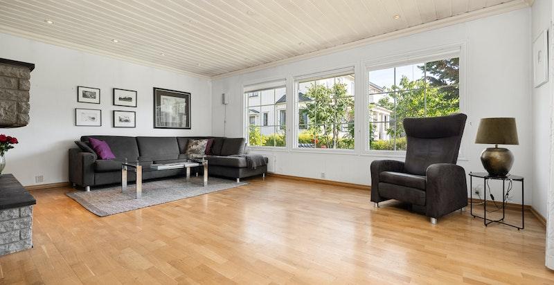 Stor stue med vinduer mot hage og utgang til terrasse