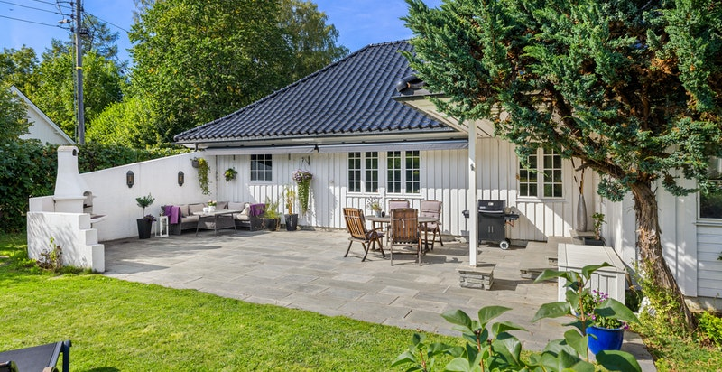 Flat og fin hagedel og stor terrasseplatting i skifer med god plass til flere møbleringsmuligheter