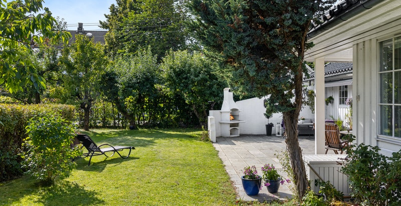 Hagen er solrik og pent beplantet med plen, busker og trær
