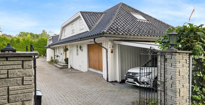 Inngangsparti med brostensbelagt gårdsplass og romslig garasje samt carport
