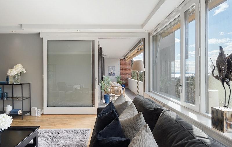 Stor stue med utgang til terrasse med fjordutsikt