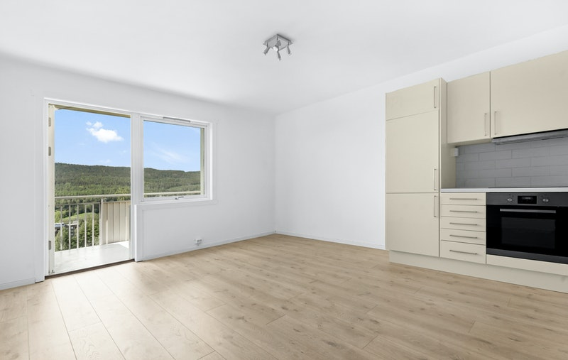 Stue/oppholdsrom med kjøkken i åpen løsning. Utgang til privat balkong med nydelig utsikt mot Nordmarka