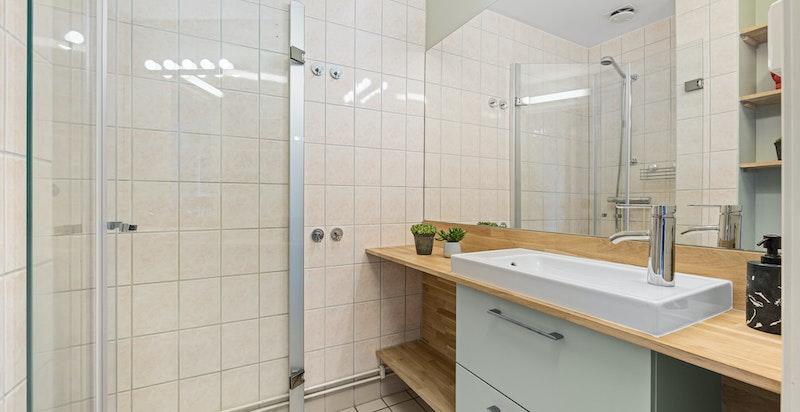 Baderommet ble påkostet i 2021 med ny heltre benkeplate i eik og nytt stort speil på veggen.