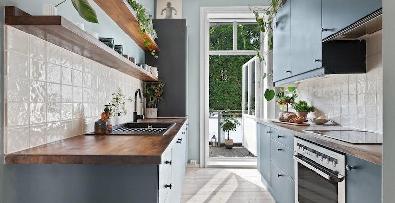 Adskilt kjøkken med generøs takhøyde, downlights og utgang til balkong.