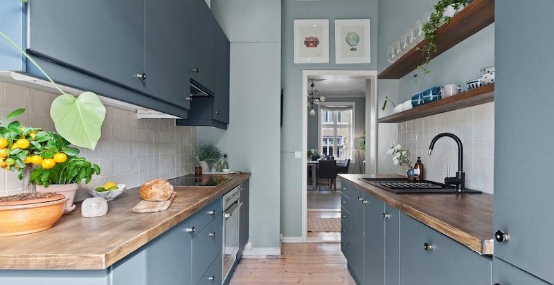 Nymalte glatte fronter i delikat blågrå farge kombinert med heltre benkeplate.