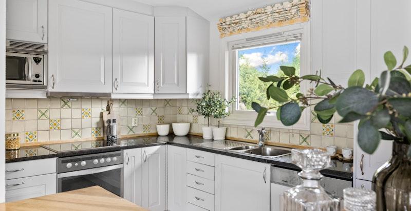 Det er hyggelig utsikt ut fra kjøkkenet og gode arbeidsflater. Integrerte hvitevarer